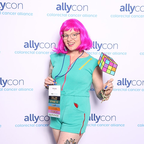 Woman with pink hair posing in front of a custom printed backdrop for Allycon